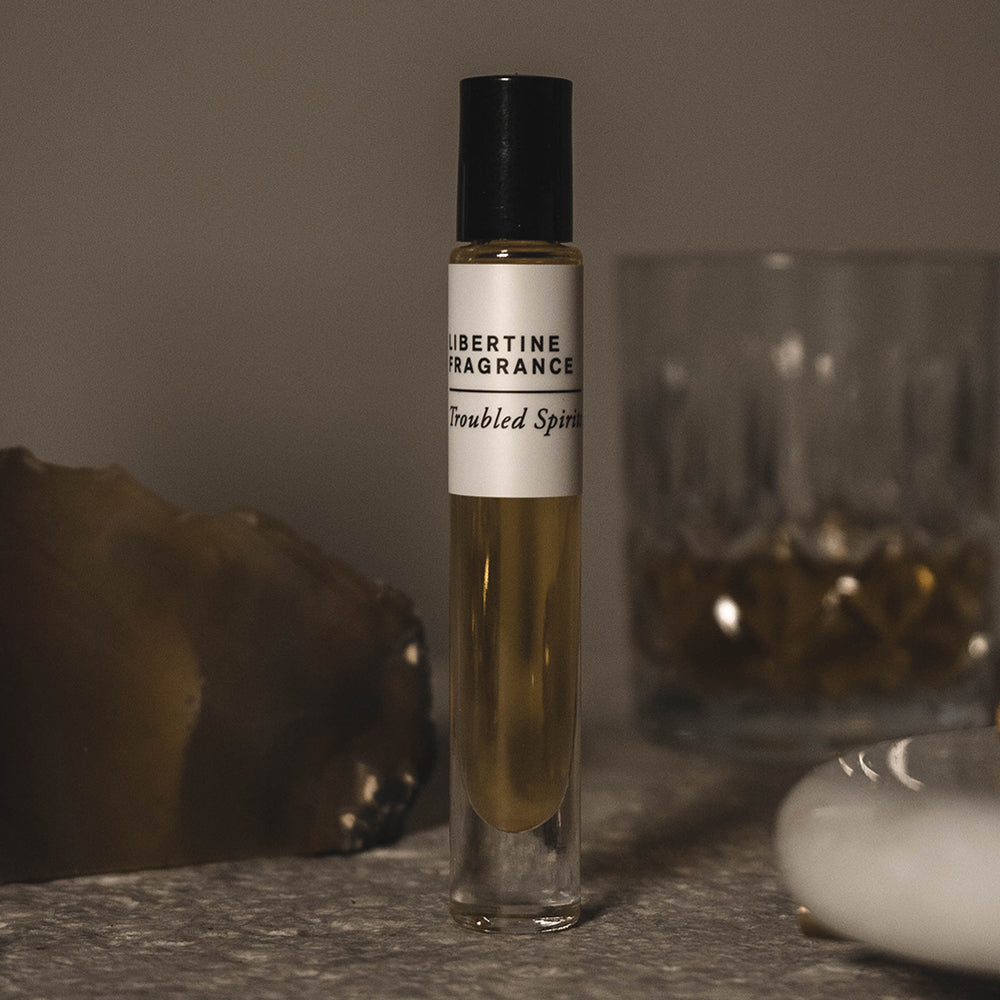boozy perfume oil bottle standing by whiskey glass