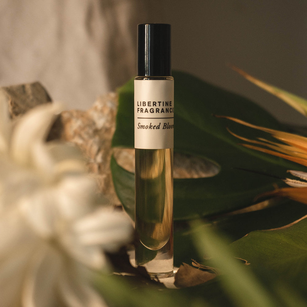 vetiver and sandalwood perfume oil on white background