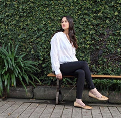 Woman sitting on bench wearing the Ten activewear black leggings with a white blouse