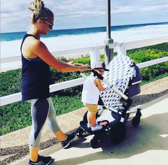 Woman in The Ten activewear pushing pram on seaside esplanade