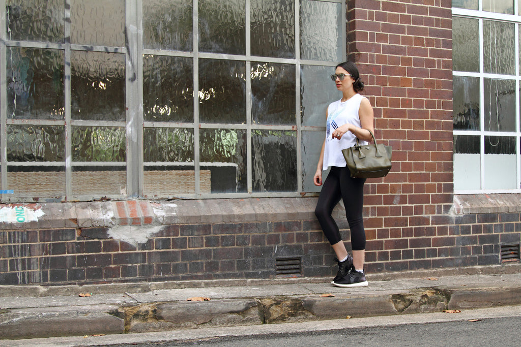 lady in stylish sustainable black pregnancy leggings leaning against a wall
