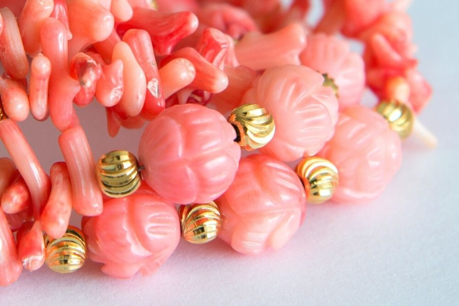 Close up of pink coral jewelry with gold beads.