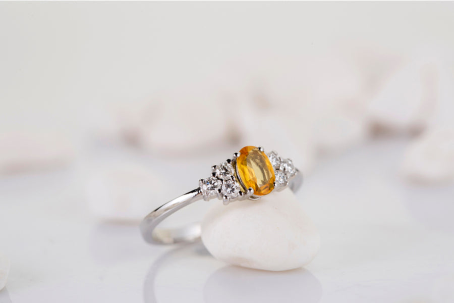 A yellow topaz ring propped up on a white background.