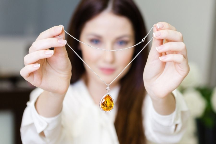 A woman holding displaying a yellow sapphire necklace.