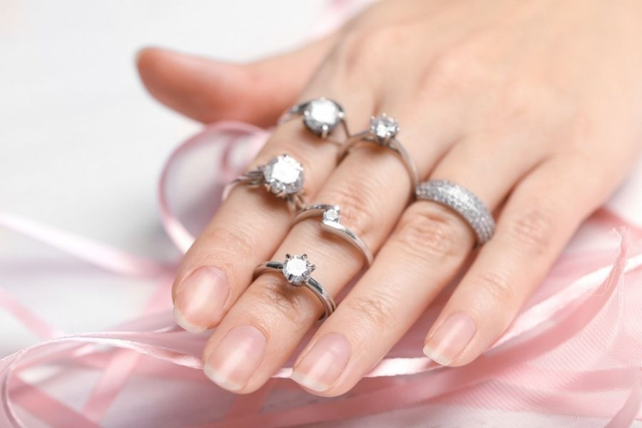 a variety of platinum diamond rings on a womans hand