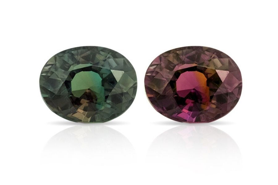 Two alexandrite stones side by side on a white background. One shows the daytime coloration, the other shows the redder nighttime coloration.