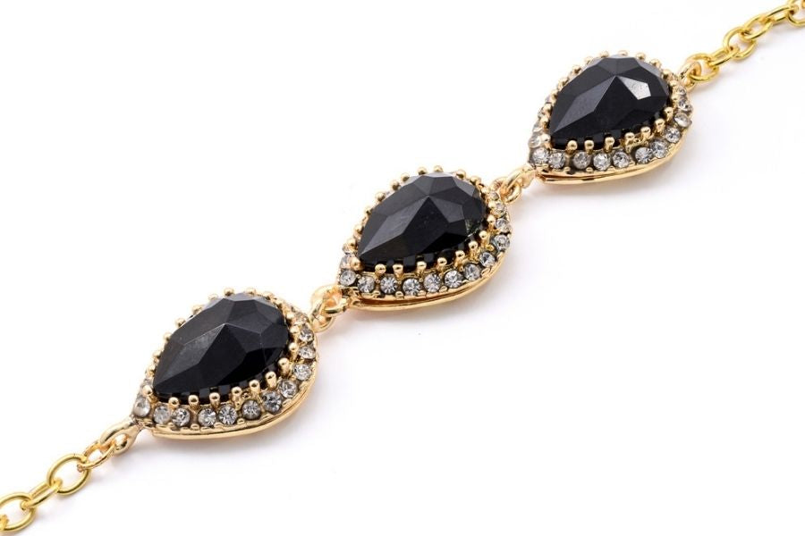 Close up of a gold bracelet with black sapphires on a white background.