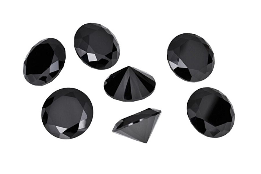 Several pieces of black zircon scattered on a white background