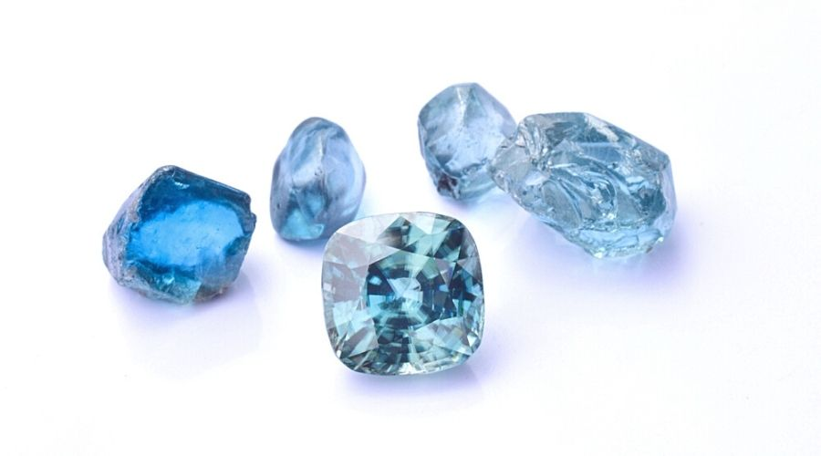 Several blue zircon stones on a white background