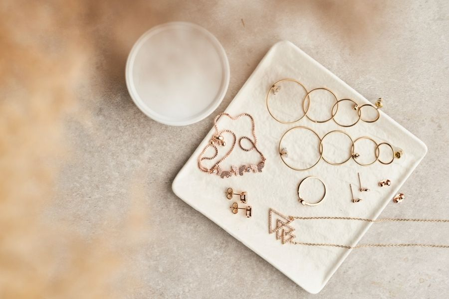 A set of gold jewelry (including rings, necklaces, and several pairs of earrings) on a white marble plate.