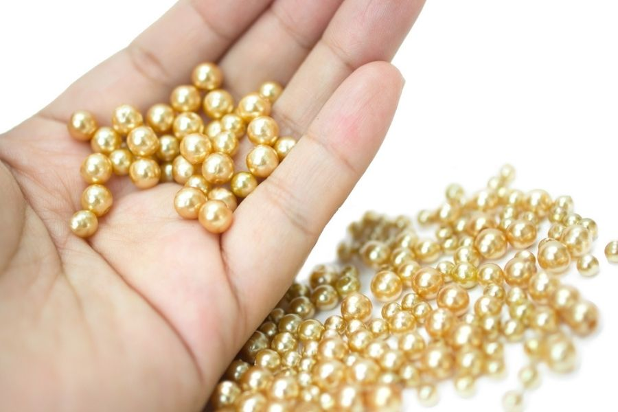 Golden pearls resting in somebody's hand on a white background.