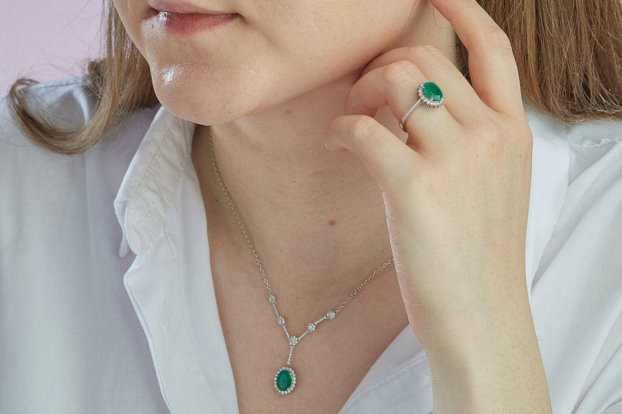 A woman wearing a green gemstone ring and necklace