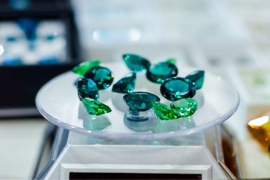 Several green topaz stones on a jewelry stand
