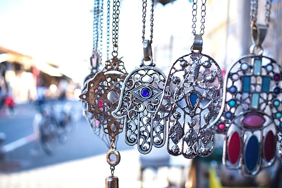 Close up of hamsa necklaces at an outdoor market
