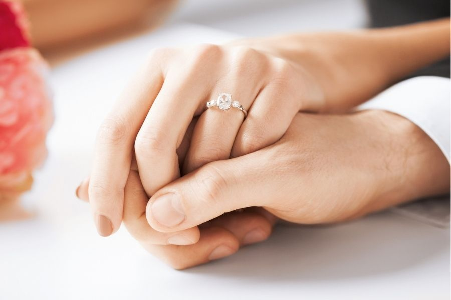 Holding hands showing diamond ring