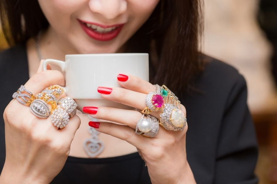 how many rings should you wear - woman with way too many rings drinking coffee