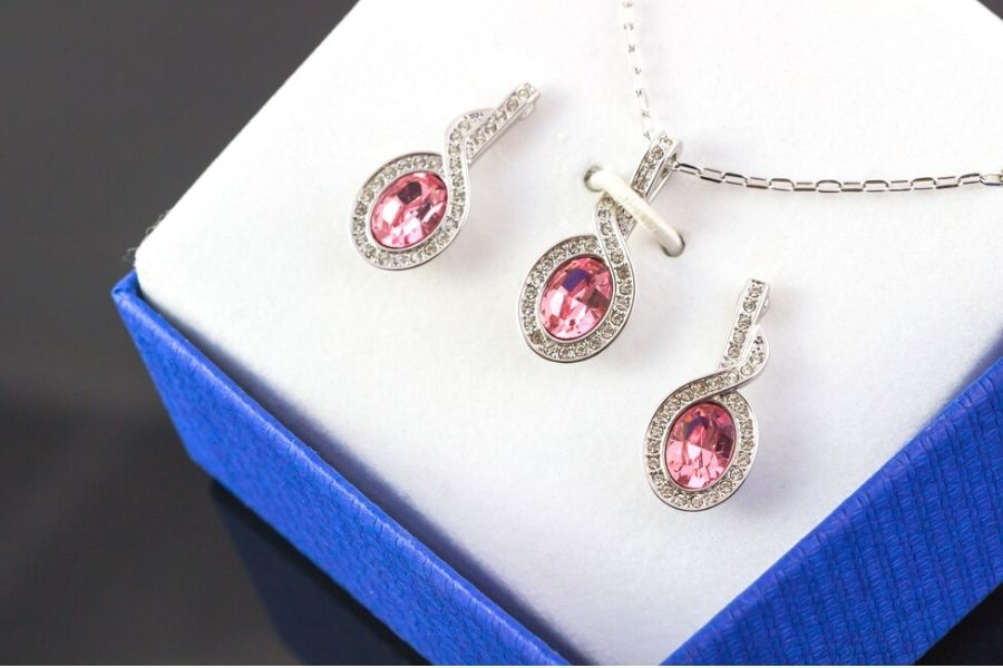 Pink gemstone necklace and earring set in a jewelry box.