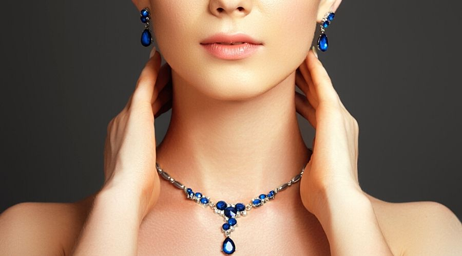 Close-up of a model wearing a blue gemstone necklace and earrings