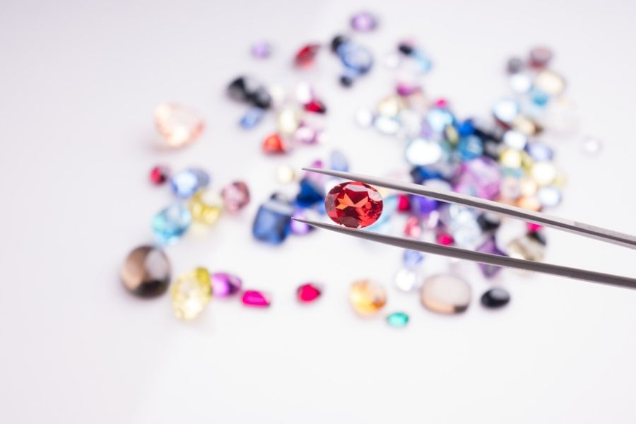 rarest diamond colors - red diamond in tweezers with other colored diamonds on the table