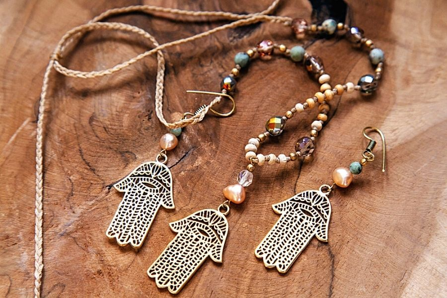 A hamsa hand jewelry set with stone beads on a wooden background
