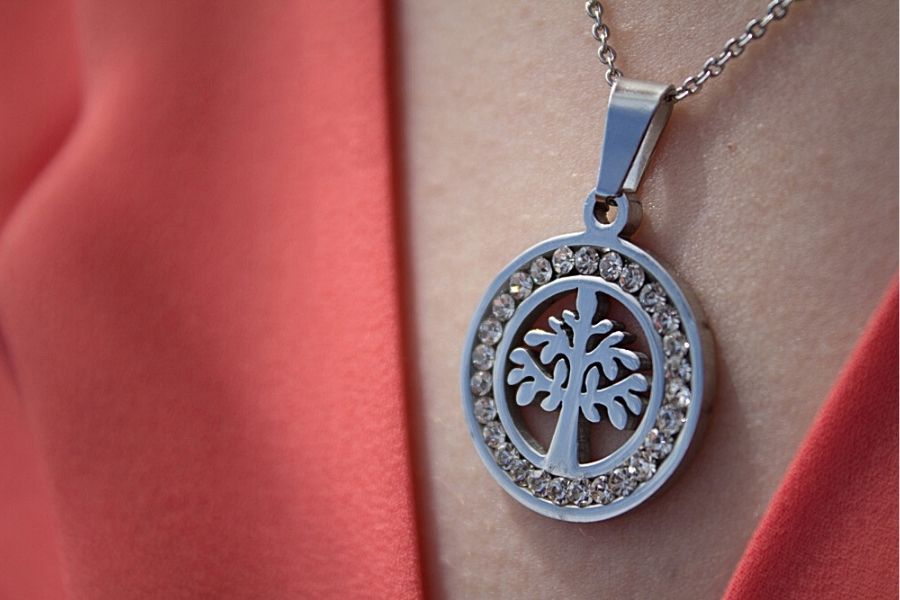 Close up of a silver tree of life necklace on a model.