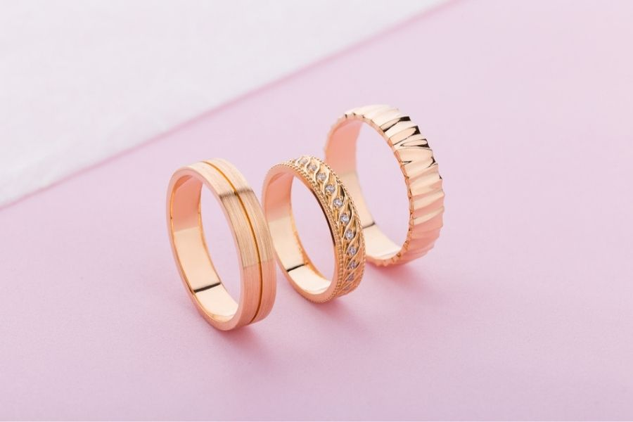 three rose gold rings on pink surface
