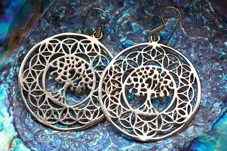 Bohemian style tree of life earrings on a blue stone background.
