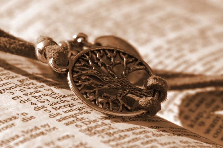 A tree of life charm resting on an open book.
