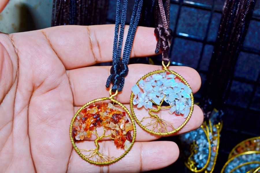 Two tree of life pendants resting in somebody's hand.