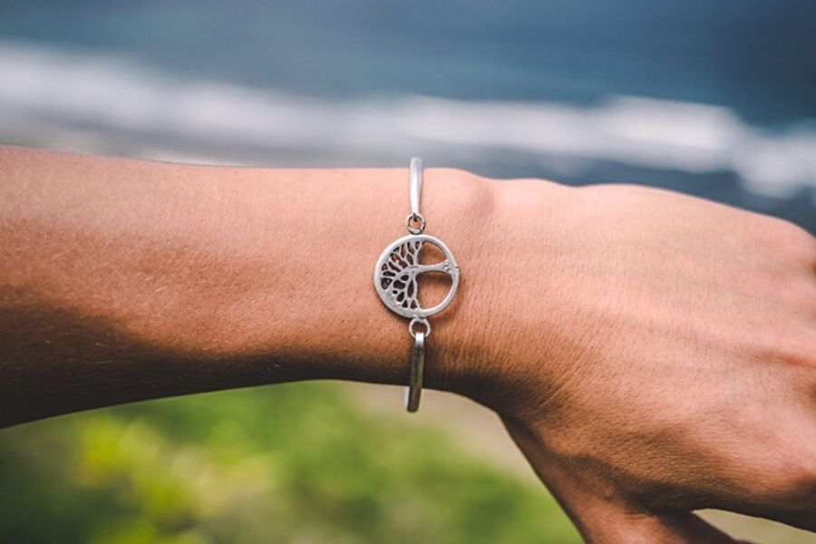 A silver tree of life bangle on somebody's wrist.