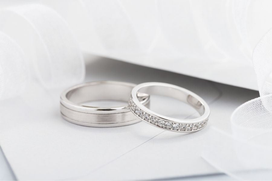 two silver engagement rings on table