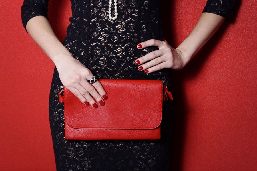 woman in black dress with red purse matching her rings to her accessories
