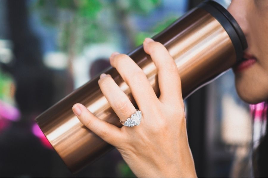 woman with a nice platinum ring drinking coffee