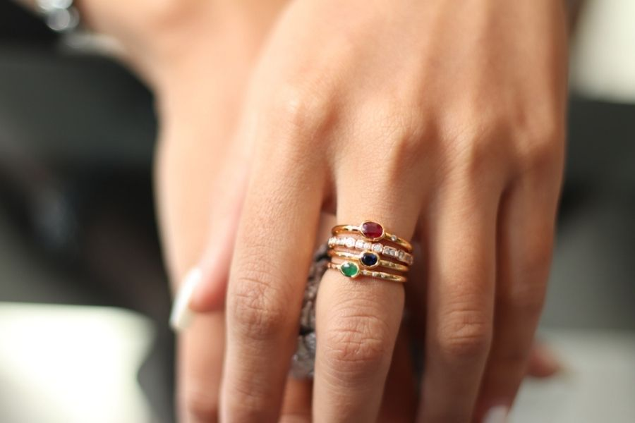 womans hands with stacked rings