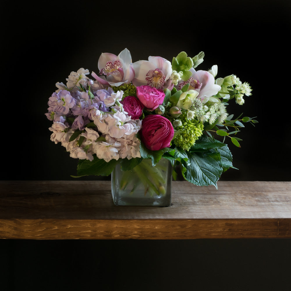 Unique boutique floral arrangement using the best premium flowers such as light pink roses, pink ranunculus, pink cymbidium orchids,, finished with mini green hydrangeas
