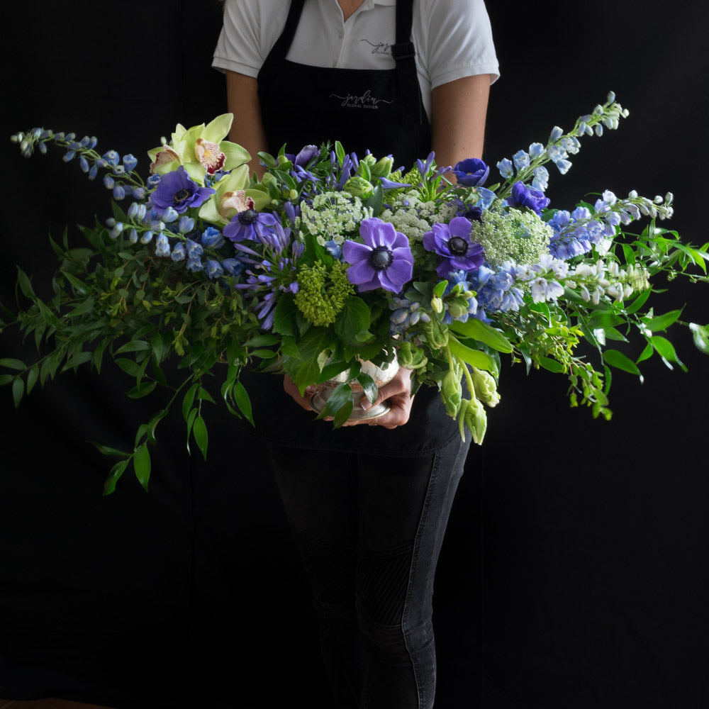 Unique  boutique floral arrangement made with the best premium flowers - purple anemones, orchids, blue stocks, and mini green hydrangeas