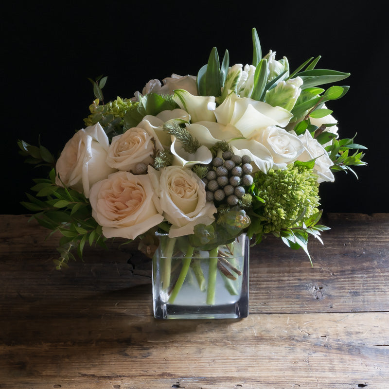 Unique boutique floral arrangement of white roses, white calla lilies, white garden roses and green flowers