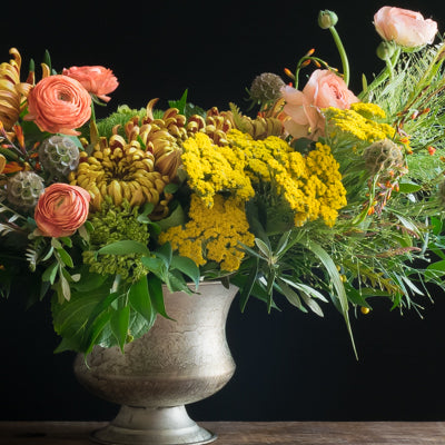 Beautiful boutique luxe fall floral arrangement of orange and yellow flowers
