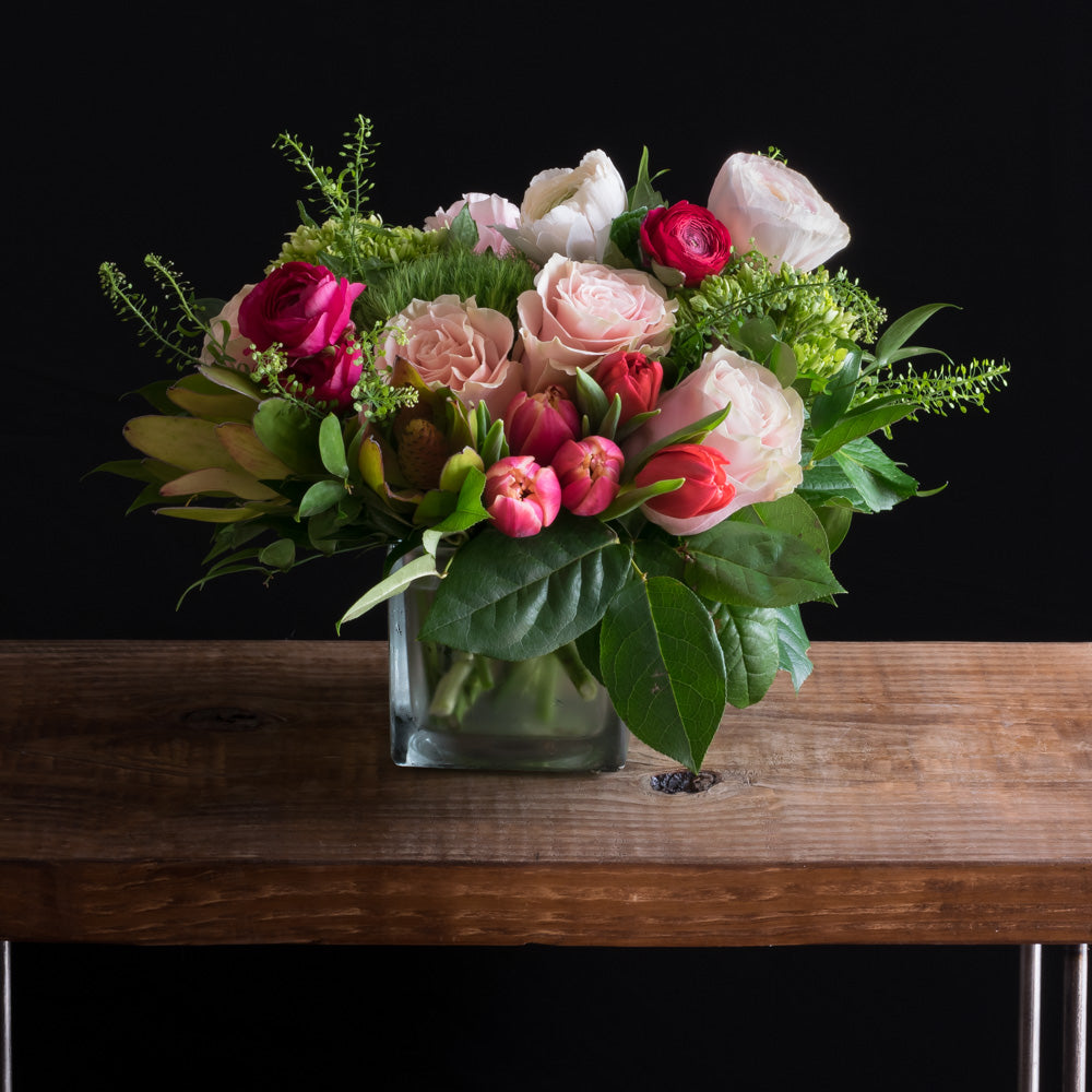 Unique boutique floral arrangement using the best premium flowers such as light pink roses, pink ranunculus, red ranunculus, pink tulips, and red roses and red tulips, finished with mini green hydrangeas
