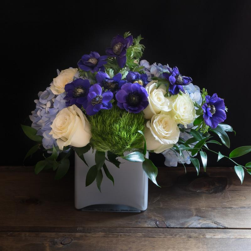 Unique blue, indigo, purple floral arrangement of hydrangeas and anemones.