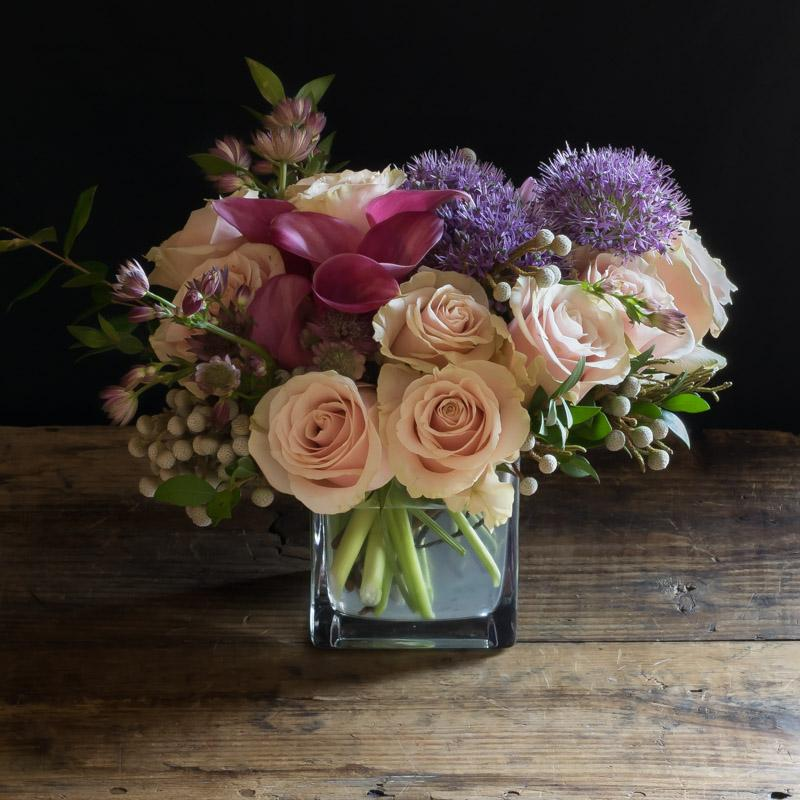 Beautiful floral design with pink roses and burgundy calla lilies