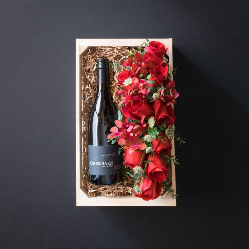 Box with wine and flowers, red roses.