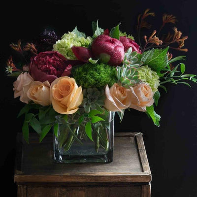 Floral design with red peonies, light orange roses, and hydrangeas