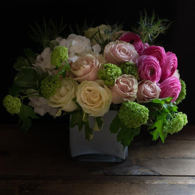 Flower arrangement of pink ranunculus, pink roses, white hydrangeas.