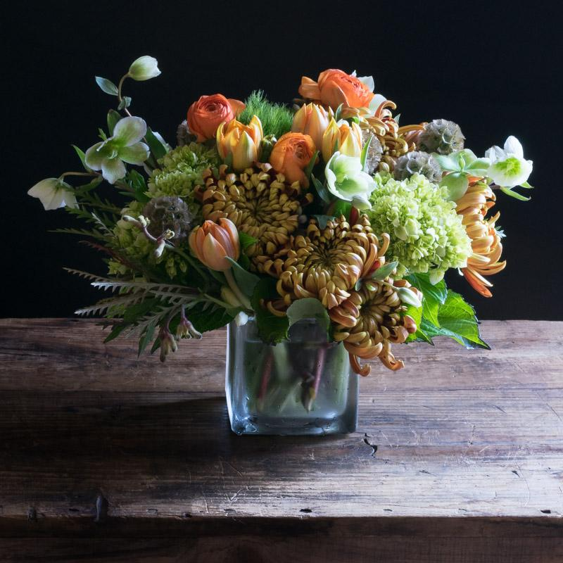 Boutique fall floral arrangement with orange roses, orange ranunculus and tulips.