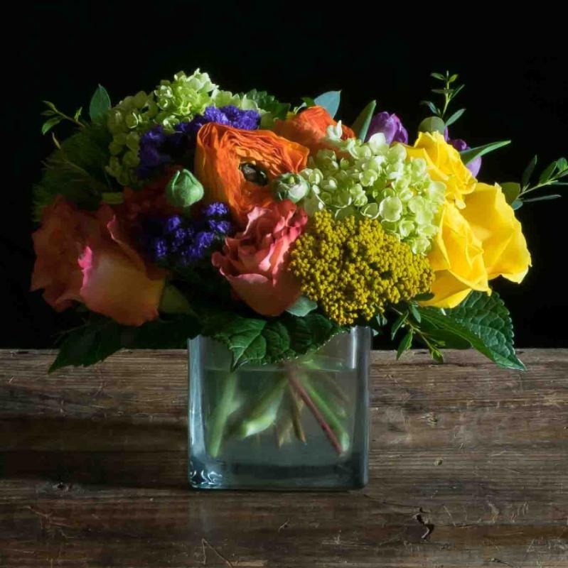 Beautiful colorful floral arrangement with pink, yellow, orange, and purple flowers.