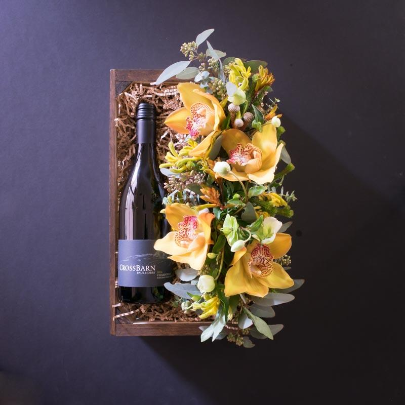 Box with wine and flowers, yellow orchids.