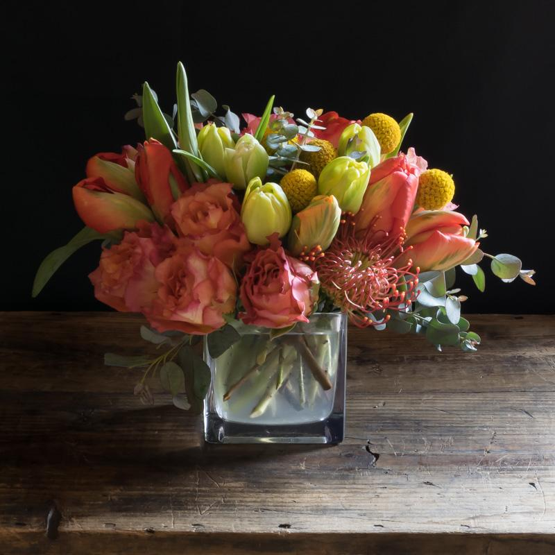 Beautiful floral design of orange garden roses, yellow tulips, and orange tulips