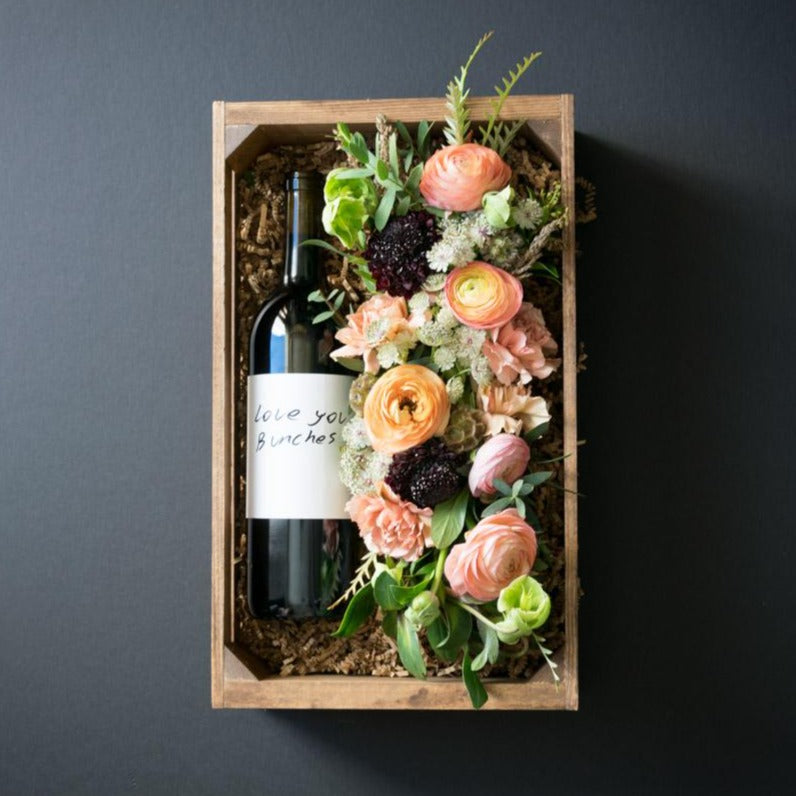 Unique boutique floral gift box combining organic red wine and floral arrangement with ranunculus, roses, and carnations