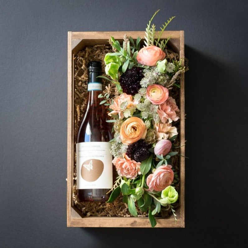 Unique boutique floral gift box combining organic red rose wine and floral arrangement with ranunculus, roses, and carnations